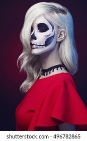 halloween make-up skull beautiful woman with blond hairstyle. Santa Muerte face girl in red dress