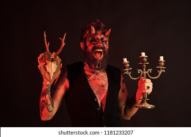 Halloween man with candlestick and satan goat skull. Devil with horns shout on brown background. Demon with red blood eyes, beard, wounds, tattoo. Idol, deity, flesh, soul concept. Occult and mystic