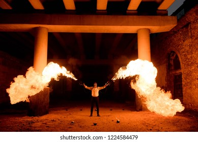 Halloween man in costume with flamethrower in his hands. Devil makeup on face for halloween party.