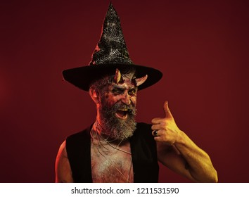 Halloween man with demon horns witch hat show thumbs up. Satan hipster smile with beard, blood, wounds on red background. Hell, death, evil, horror concept. Might, magic, witchcraft