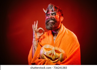 Halloween man devil hold pumpkin on red background. Satan grin with bloody horns, beard, blood, wounds. Darkness and light concept. Demon in blanket show ok gesture with jack o lantern. Trick or treat