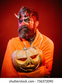 Halloween man devil hold pumpkin on red background. Satan with bloody horns, beard, blood, wounds. Demon in blanket with jack o lantern. Darkness and light concept. Trick or treat.