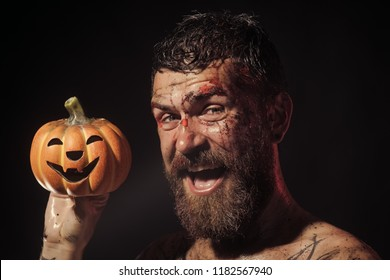 Halloween man with jack o lantern smile on black background. Happy hipster with bloody beard hold pumpkin. Magic, enchantment, witchcraft. Wizard, sorcerer, warlock. Halloween, holidays celebration