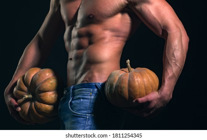 Halloween man, party poster or greeting card. Shirtless athletic man hold pumpkin turned back on black background