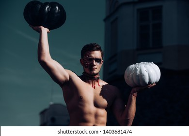 Halloween man with pumpkin in the street. Day of The Dead. Halloween. Death - young man Halloween portrait. The scary zombie is in the street with pumpkin. Hot guy. Fitnes
