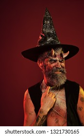 Halloween man with satan horns in witch hat on head. Devil hipster with beard, blood, wounds on face on red background. Hell, death, evil, horror concept. Might, magic, witchcraft
