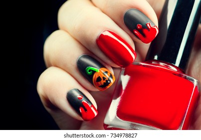 Halloween manicure design ideas. Halloween Nail art design. Nail Polish. Beauty Trendy Stylish Colorful Nails and Nailpolish. Black matte nailpolish with blood drips and pumpkin. Isolated on black.