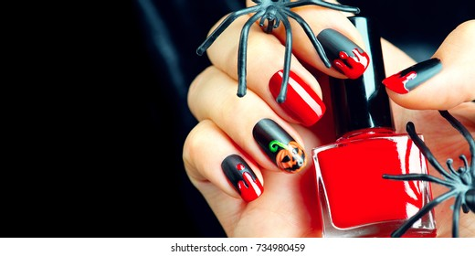 Halloween manicure design ideas. Halloween Nail art design. Nail Polish. Beauty hands. Trendy Stylish Nails and Nailpolish bottle. Black nailpolish with blood drips and pumpkin. Isolated on black.