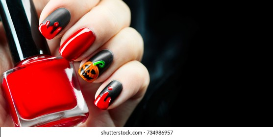 Halloween manicure design ideas. Halloween Nail art design. Nail Polish. Beauty hands. Trendy Stylish Colorful Nails and Nailpolish bottle. Black polish with blood dops and pumpkin. Isolated on black.