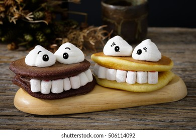 Halloween marshmallow and monster teeth smiling happily on a black plate