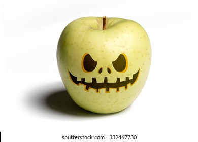 Halloween mask on a green apple