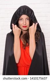 Halloween masquerade. Halloween party. Damn pretty woman devil. Death in black cloak symbol. Vampire in cloak sexy devil girl. Woman tempting vampire demon. Girl covered with cloak. Devil concept.