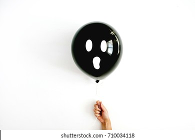 Halloween minimal concept. One black balloon with scary face in girl's hand. Flat lay, top view.