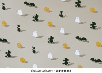 Halloween minimal pattern maed with paper ghost, pumpkin, witch, bat and car. Autumn holiday concept background