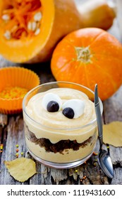 Halloween monster dessert with marshmallow eyes from pumpkin cream and chocolate cookies in a glass, Halloween treats idea for kids