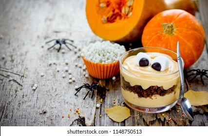 Halloween monster dessert with marshmallow eyes from pumpkin cream and crushed chocolate cookies in glass on wooden table