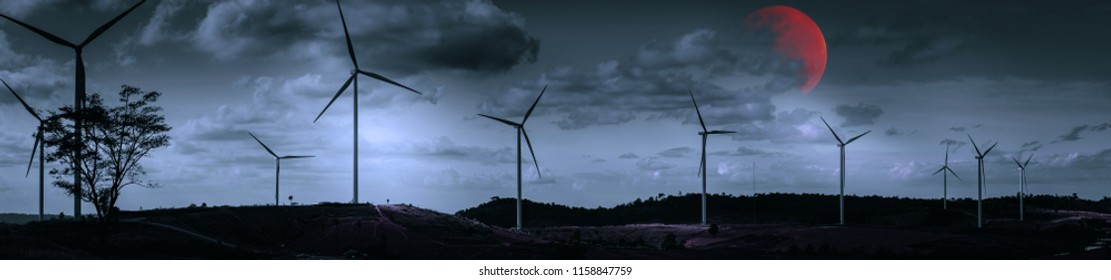 Halloween moon and sky concept from panorama view of wind turbine construction in field and meadow look like cross with red moon with horror scene sky and cloudy background