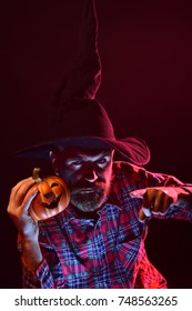 Halloween mystery and nightmare concept. Magic illumination and jack o lantern. Man in witch hat holding pumpkin in dark. Autumn holiday celebration. Sorcerer with beard pointing finger in red light.