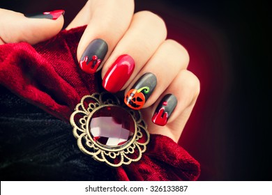 Halloween Nail art design. Nail Polish. Beauty hands. Trendy Stylish Colorful Nails and Nailpolish. Black matte nailpolish with blood drips and pumphin