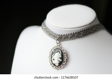 Halloween necklace with skull cameo pendant on a dark background close up