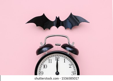 Halloween night concept. Black alarm clock and flying bat on pink background, closeup. Creative flat lay, top view, template for yuor design, greeting card, invitation.
