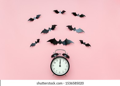 Halloween night concept. Black alarm clock and flying bats on pink background. Creative flat lay, top view, template for yuor design, greeting card, invitation.