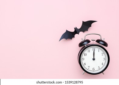 Halloween night concept. Black alarm clock and flying bat on pink background. Creative flat lay, top view, copy space, template for yuor design, greeting card, invitation.