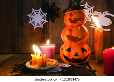 Halloween night decoration Jack-o pumpkin head lantern with old candle light and spider web on wood texture background
