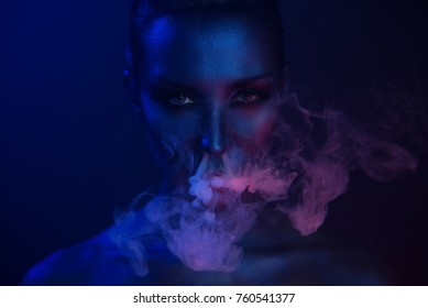 Halloween night. Horror Vape Party. Beautiful Sexy Young vamp Woman with glamorous mystical makeup vaping in Nightclub (exhaling smoke). Girl smoking in Club. Blue mystic smoke