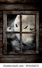 Halloween night ravens flying in front the moon and clouds, view through an old wooden cabin window