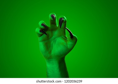 Halloween, nightmare creature and evil monster horror story concept with a scary zombie or demon hand with creepy long black nails isolated on green with a clip path cutout
