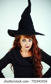 Halloween old lady in witch hat. Halloween holiday celebration. woman in black with long red hair and makeup. traditional party. old woman on white background.