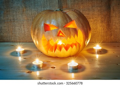 Halloween orange pumpkin jack lantern with candles on a wooden background in a rustic style. Beautiful autumn Pumpkins Halloween background with place for text