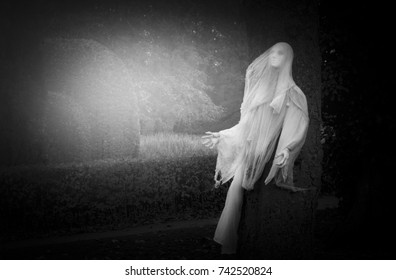Halloween outdoor decoration in the garden with decorated by white ghost wearing white cloth in black and white,Old American trick-or-treat Halloween tradition,Halloween background concept