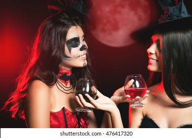 Halloween party 2016! Fashion women like witch holding cocktail of blood. Makeup. Halloween costumes. Role. Witch carnival costume. Role-playing games. Sexy babes. Night with big full moon