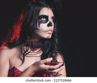 Halloween party 2018. Beautiful woman like witch holding cocktail of blood. Halloween costumes and makeup. Witch carnival costume. Night with big full moon