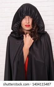 Halloween party. Damn pretty woman devil. Death in black cloak symbol. Vampire in cloak sexy devil girl. Woman tempting vampire demon. Girl covered with cloak. Devil concept. Halloween masquerade.