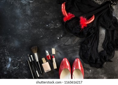 Halloween party female outfit accessories: devil horns, red shoes, make up, brushes. Flat lay, top view, copy space, square