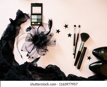 Halloween party female outfit accessories: black on pastel pink, make up, eye shadow, brushes, shoes, cloth. Flat lay, top view, copy space, square