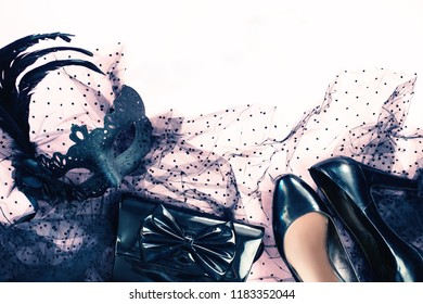 Halloween party female outfit accessories: black on pastel pink, purse, mask, shoes, cloth. Flat lay, top view and copy space