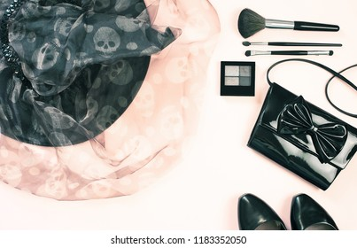 Halloween party female outfit accessories: black on pastel pink, witch hat, purse, make up eye shadow, brushes, shoes, cloth. Flat lay top view copy space.