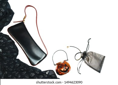 Halloween party female outfit layout of accessories black on white background: shoes, handbag, cloth with skulls, jewelry and glass pumpkin. Flat lay, top view. Party Black Friday concept. Isolated.