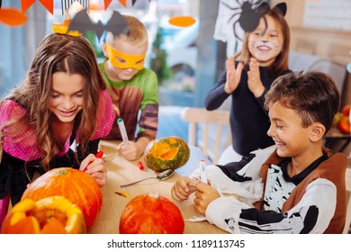 Halloween party. Four good-looking beaming children attending Halloween celebration coloring pumpkins together