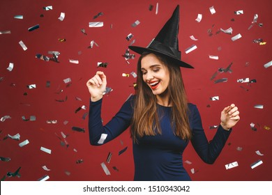 Halloween Party girl. Happy Halloween Witch with bright make-up and long hair. Beautiful young surprised woman posing in witches sexy costume. Isolated on red background with confetti.