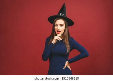 Halloween Party girl. Happy Halloween Witch with bright make-up and long hair. Beautiful young surprised woman posing in witches sexy costume. Isolated on red backgroun.