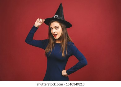 Halloween Party girl. Happy Halloween Witch with bright make-up and long hair. Beautiful young surprised woman posing in witches sexy costume. Isolated on red background.