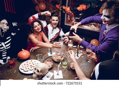 Halloween party. The guy in the Joker costume spills his champagne glasses in glasses. They are sitting at a table in a nightclub for Halloween. On the table are sweets