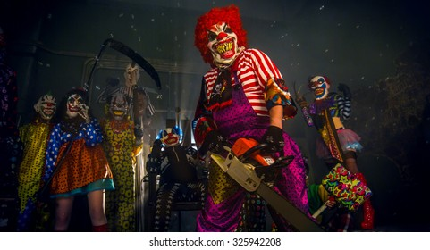 Halloween party horror clowns. The clown in the red wig standing with a chainsaw.