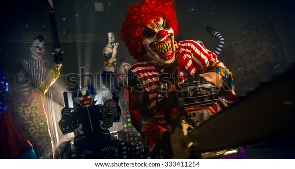 Clowns d'horreur de fête d'Halloween. Le clown dans la perruque rouge se tenant avec une tronçonneuse.