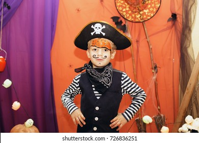 Halloween party. A little boy in a pirate costume and a makeup on his face is having a good time at the Halloween party. Face painting kids. Child among halloween decorations